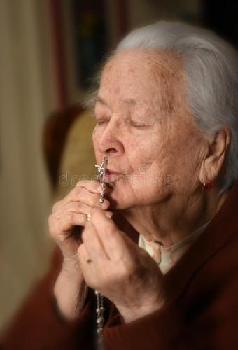 donna-anziana-che-prega-e-che-tiene-rosario-d-argento-90342508